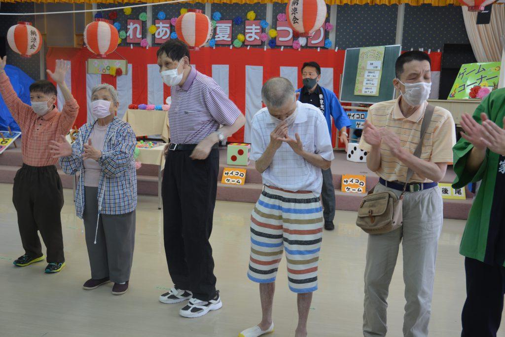 講堂で盆踊りを踊る利用者達の写真