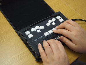 ブレイルメモで点字を打つ利用者