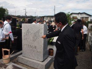 墓碑の言葉を説明する理事長