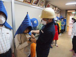 防災頭巾のかぶり方を確認する職員